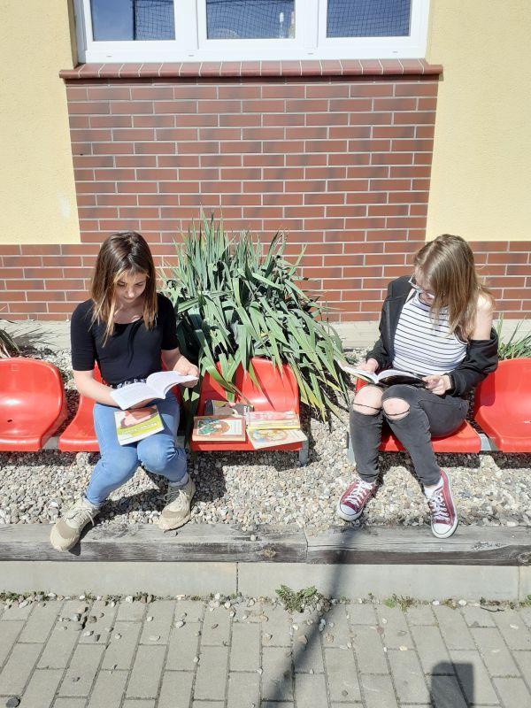 Dwie nastolatki oglądają książki Małgorzaty Musierowicz siedząc przed biblioteką.