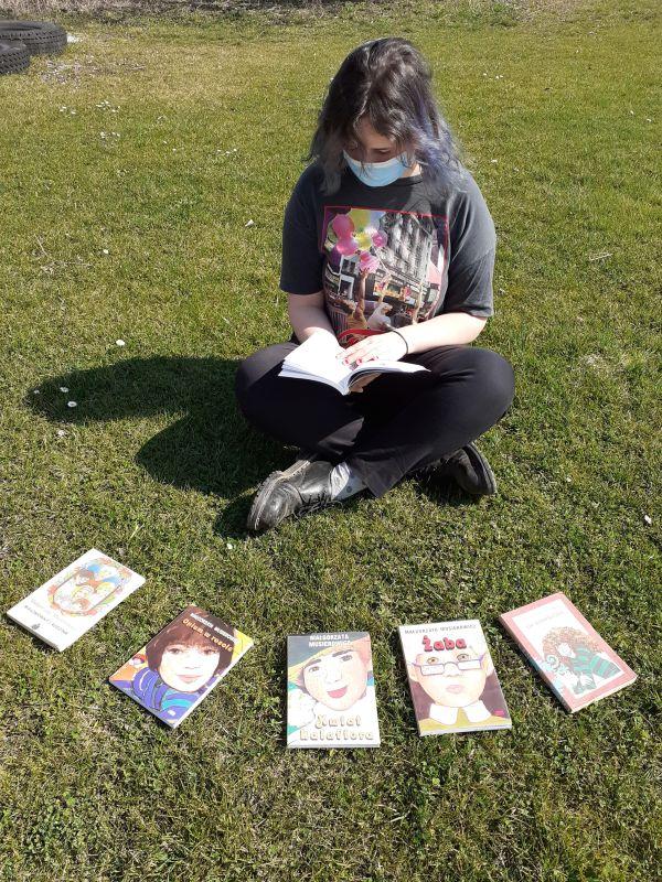 Nastolatka siedzi na trawie i czyta książkę Małgorzaty Musierowicz.