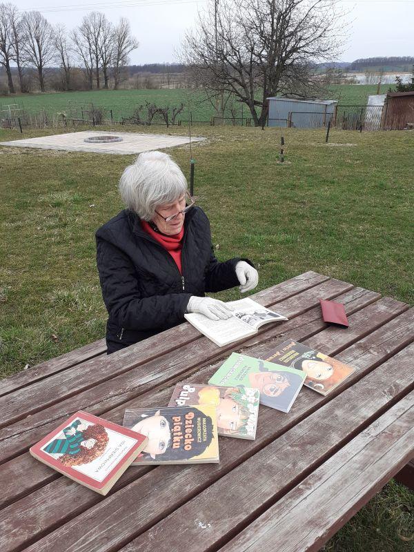 Na dworze przy drewnianym stole siedzi seniorka czytająca książki Małgorzaty Musierowicz.