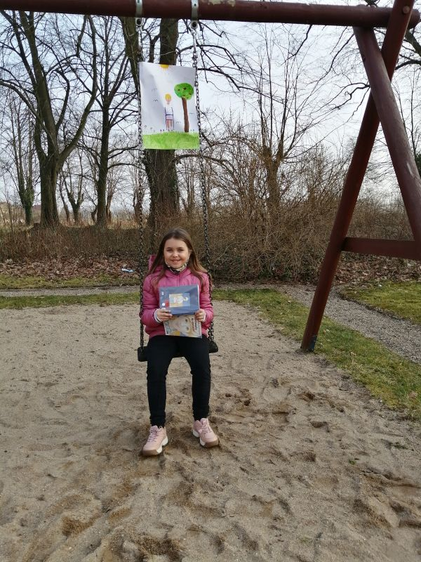Uśmiechnięta dziewczynka prezentuje książkę Małgorzaty Musierowicz siedząc na huśtawce.