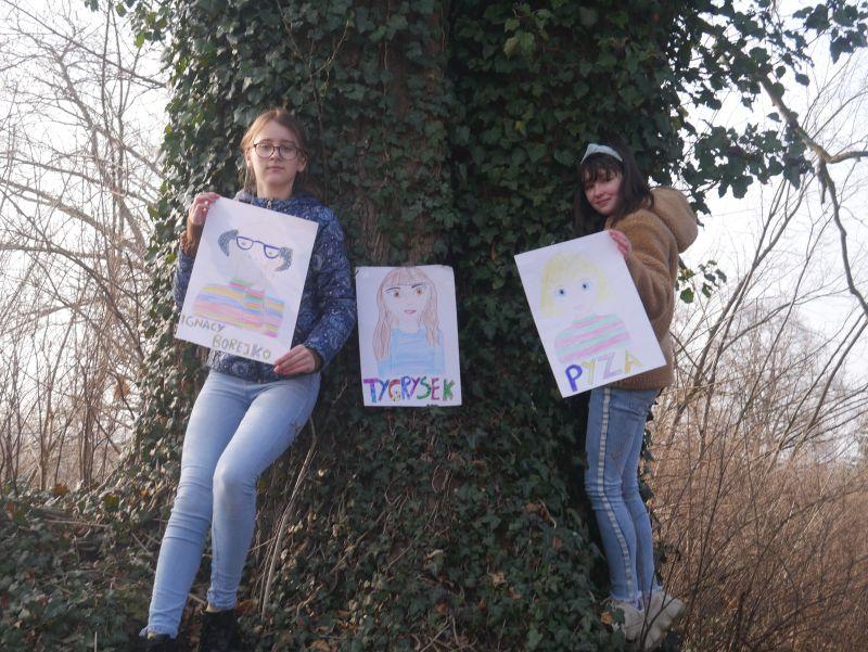 Dwie dziewczynki prezentują trzy portrety bohaterów książek Małgorzaty Musierowicz stojąc pod drzewem.