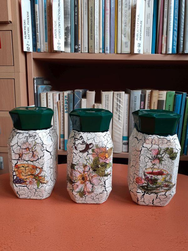 Trzy pojemniki stojące na stole, pomalowane w kwiaty techniką decoupage