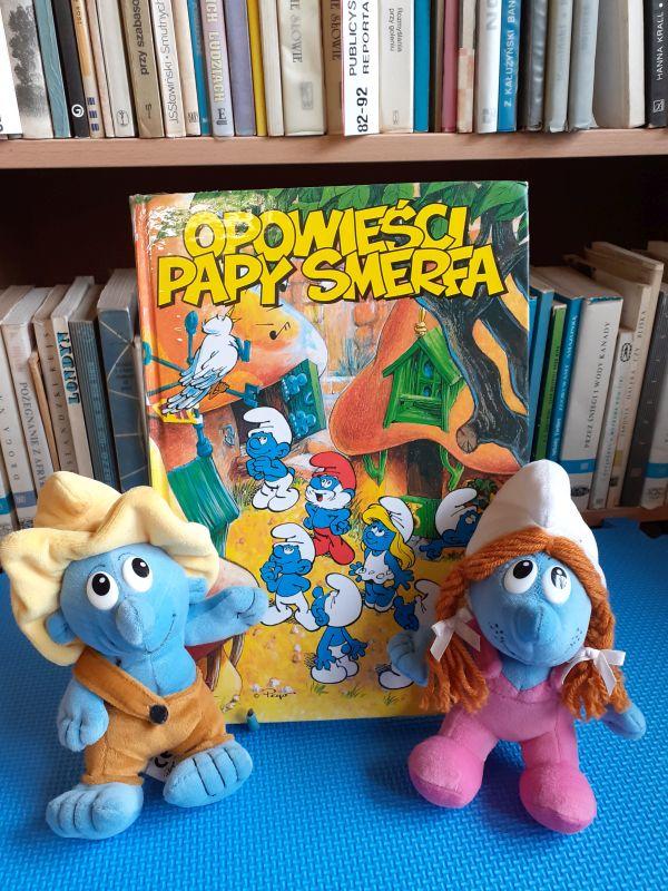 Książka o smerfach i dwie maskotki smerfów stojące po bokach.