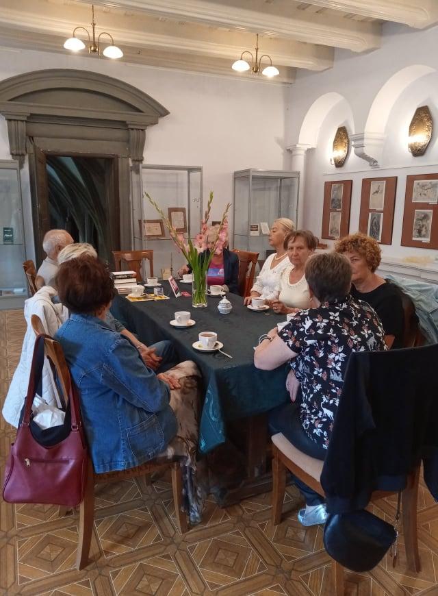 Grupa osób siedzących przy stole dyskutuje na temat przeczytanej książki. Na stole leży zielony obrus. Stoją na nim białe filiżanki z herbatą i wazon z różowymi kwiatami oraz książki.
