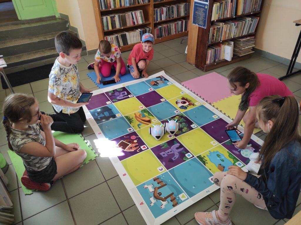 Grupa dzieci siedząca na podłodze bawi się robotami do nauki kodowania.