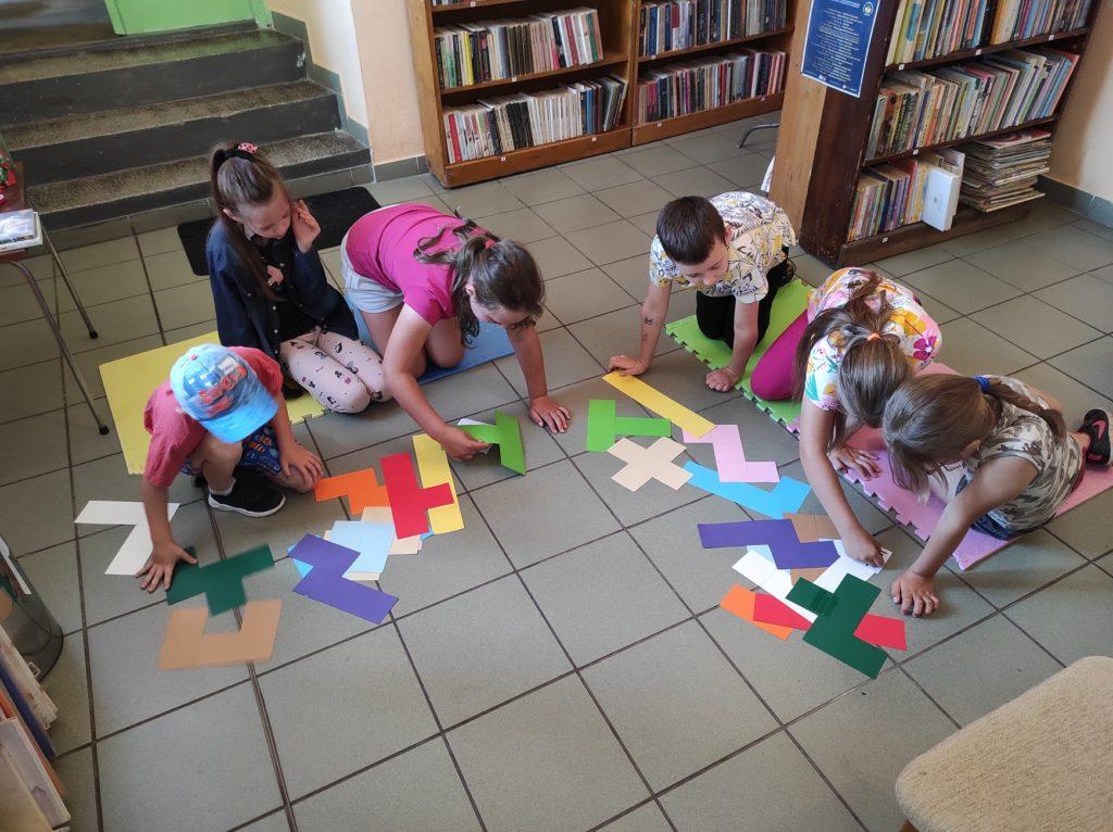 Grupa dzieci siedzi na podłodze i układa kolorowe puzzle.
