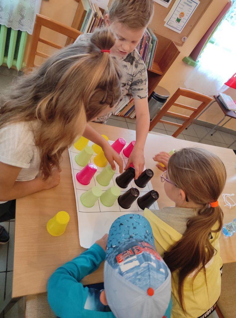 Czworo dzieci siedzi przy stole i układa kolorowe, plastikowe kubeczki.