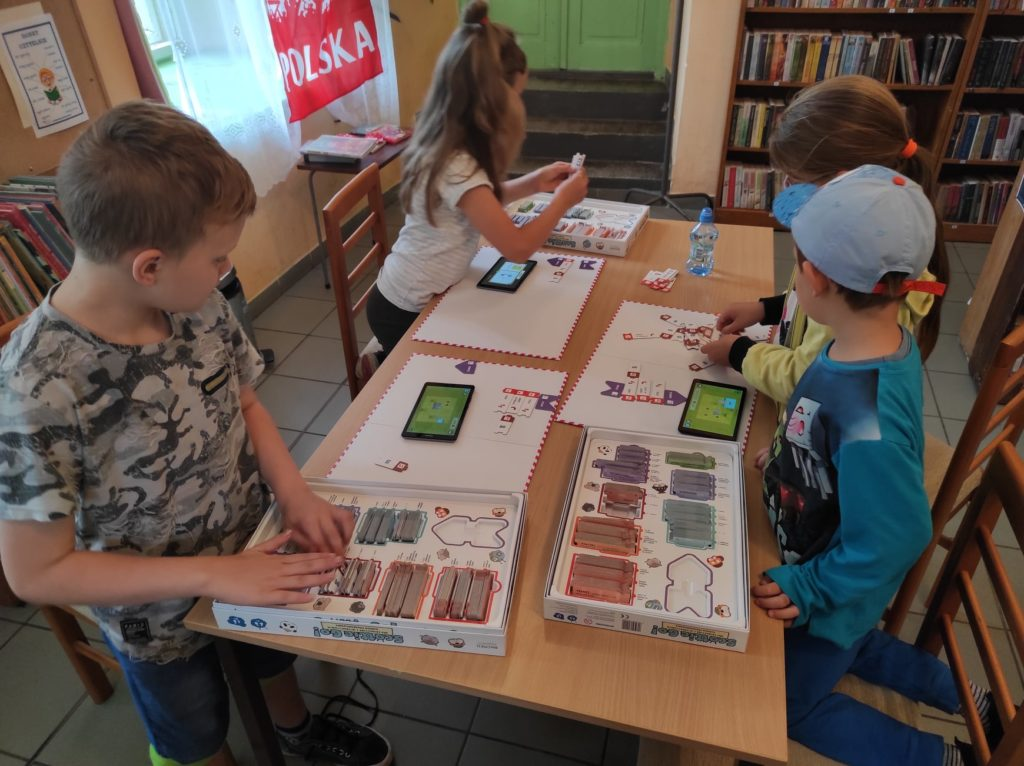 Czworo dzieci siedzi przy stole i gra w grę do nauki kodowania.