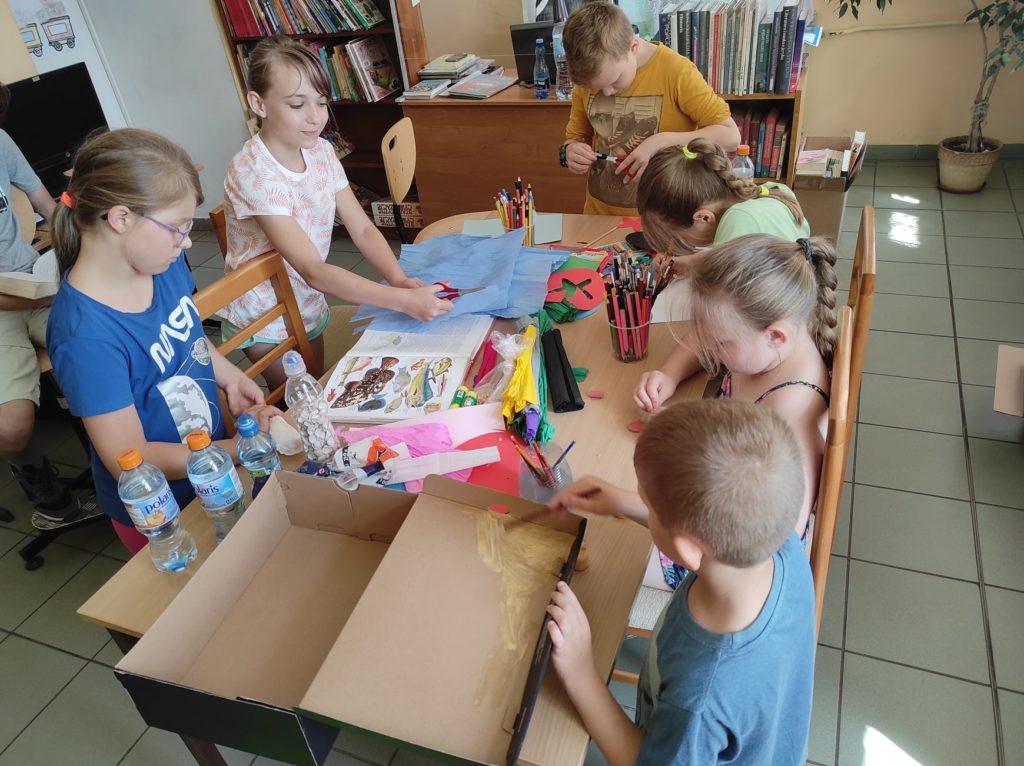 Grupa dzieci siedzi przy stole w trakcie zajęć plastycznych i robi papierowe zwierzęta wodne.