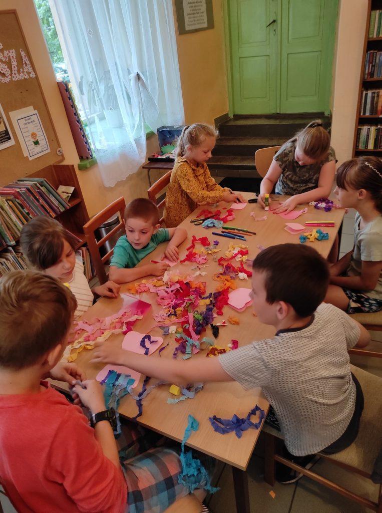 Grupa dzieci siedzi przy stole i robi meduzy z papieru i bibuły.