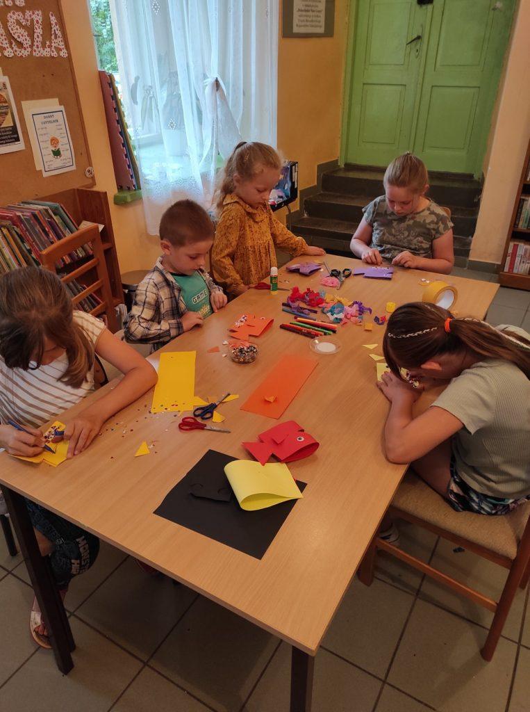 Grupa dzieci siedzi przy stole i robi ryby z papieru, udekorowane cekinami.