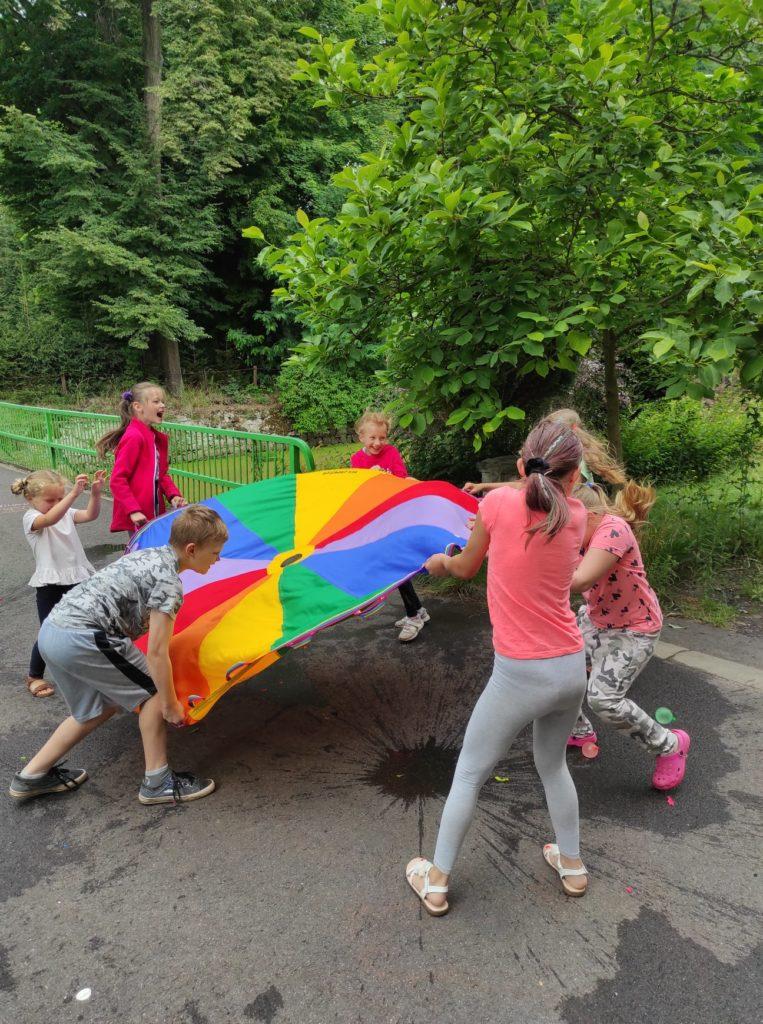 Grupa dzieci bawi się kolorową chustą.