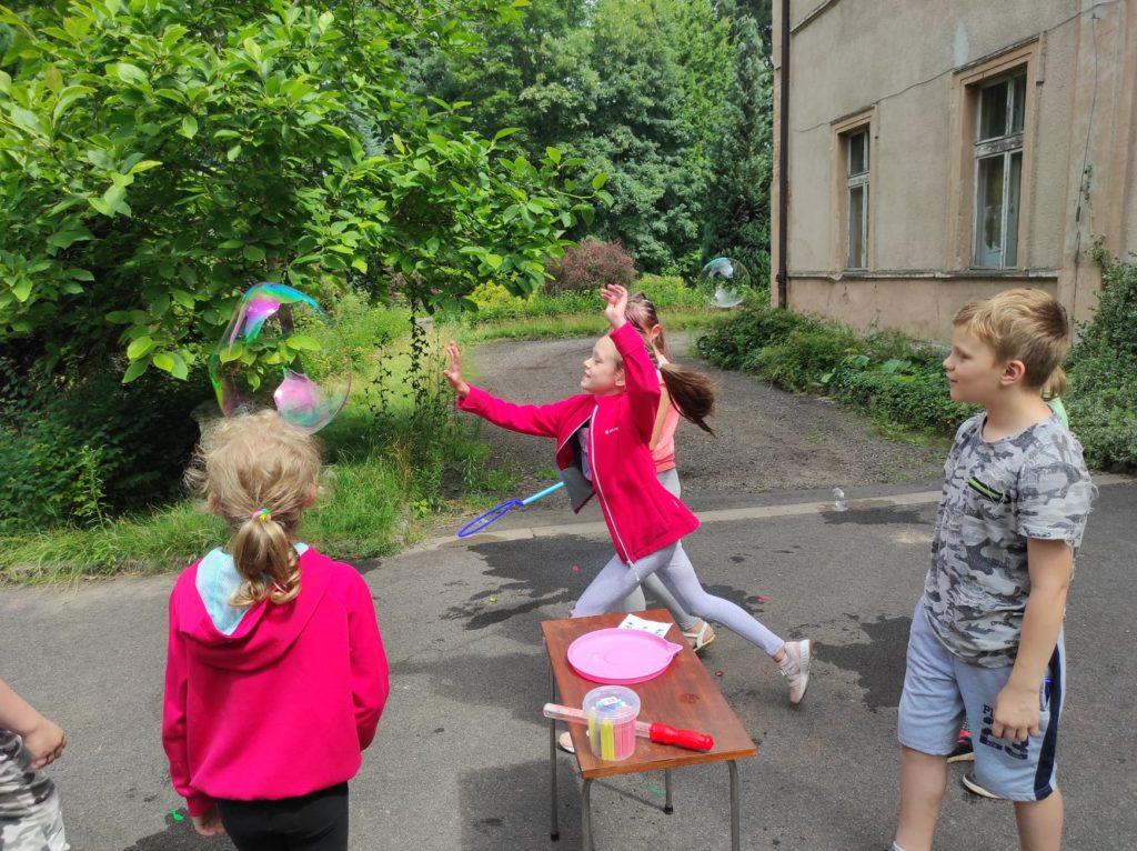 Grupa dzieci puszcza bańki mydlane.