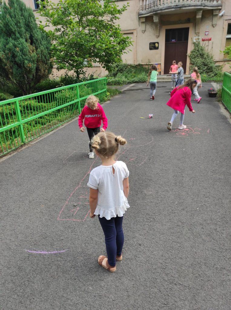 Grupa dzieci maluje kredą na asfalcie.