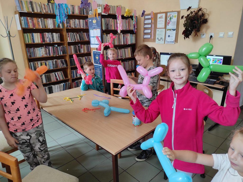Grupa dzieci pokazuje własnoręcznie wykonane balonowe zwierzaki.