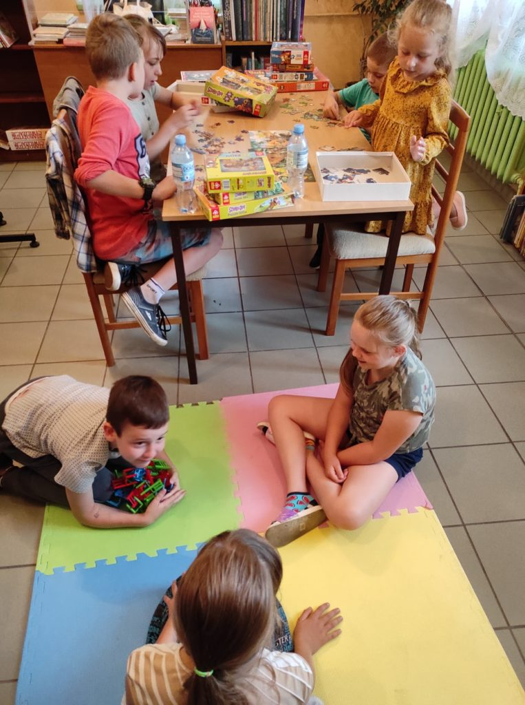 Grupa dzieci siedząca przy stole i na podłodze grająca w gry planszowe oraz układająca puzzle.