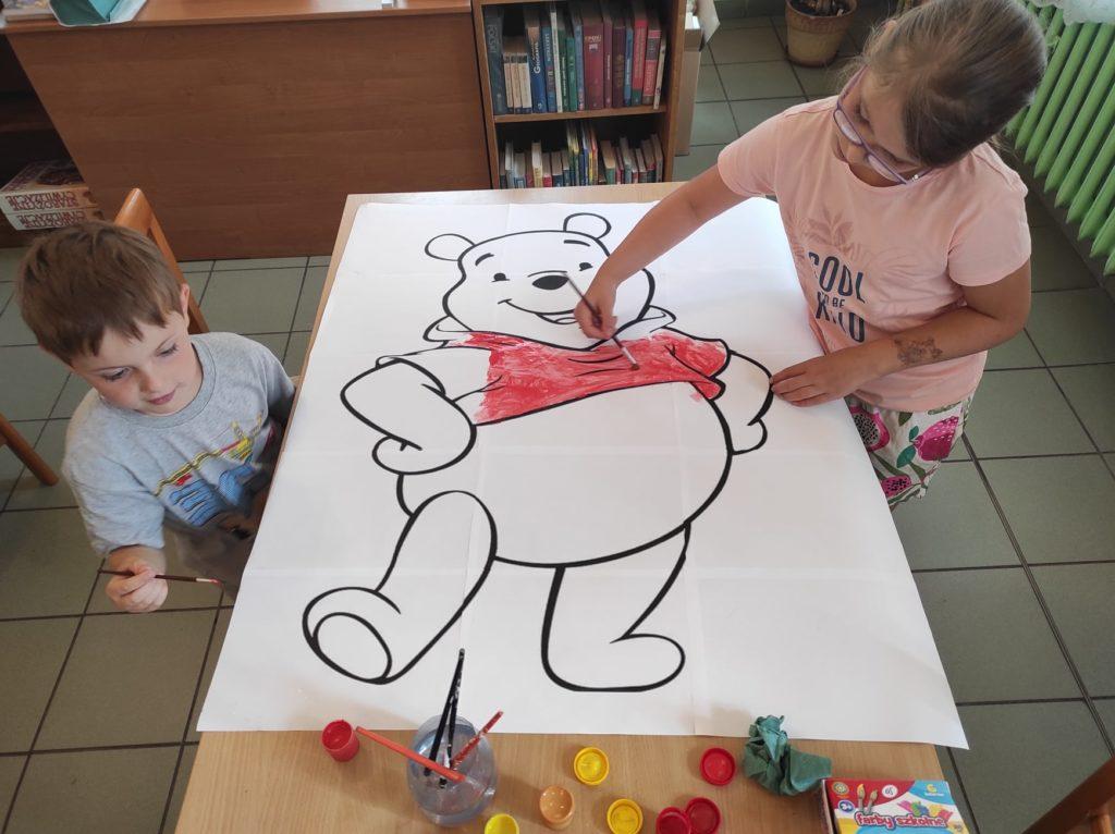 Dwoje dzieci maluje farbami kolorowankę.